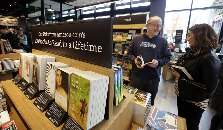Customer Jeff Edward, left, talks with Amazon employee Sarah Gelman as Edward shops at the opening day for Amazon Books, the first brick-and-mortar retail store for online retail giant Amazon, Tuesday, Nov. 3, 2015, in Seattle. The company says the Seattle store, coming two decades after it began selling books over the Internet, will be a physical extension of its website, combining the benefits of online and traditional book shopping. Prices at the store will be the same as books sold online. (AP Photo/Elaine Thompson)