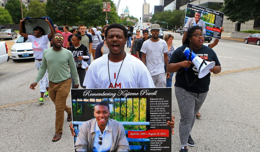 FILE - In this Aug. 19, 2015 file photo, Mike Hassell, center, leads a march to St. Louis' municipal courthouse on the one-year anniversary of the shooting death of Kajieme Powell by St. Louis police officers. St. Louis' city prosecutor says Tuesday, Nov. 3, 2015 that two police officers who fatally shot Powell, who  was  armed with a steak knife, were justified in opening fire and won't face charges. (Christian Gooden/St. Louis Post-Dispatch via AP, File)  EDWARDSVILLE INTELLIGENCER OUT; THE ALTON TELEGRAPH OUT; MANDATORY CREDIT