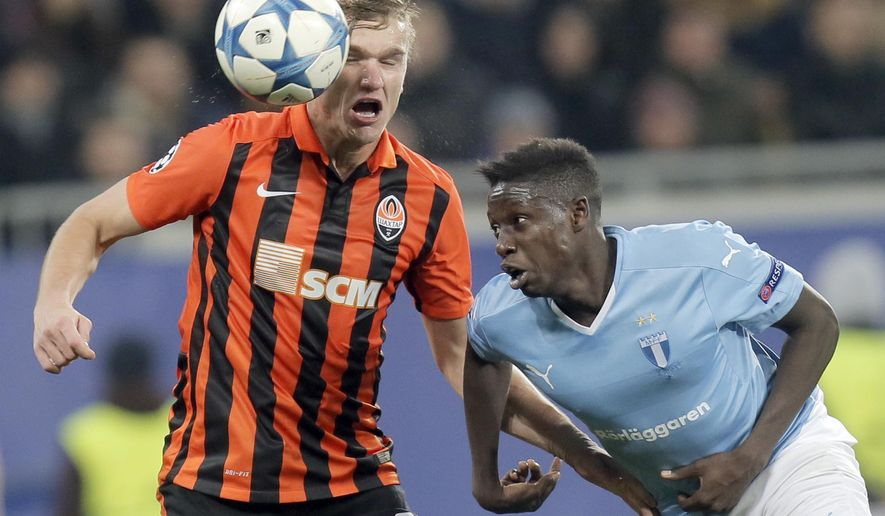 Shakhtar's Oleksandr Hladkiy, left, goes for a header with Malmo's Pa Konate during the Champions League Group A soccer match between FC Shakhtar and Malmo at Arena Lviv stadium in Lviv, western Ukraine, Tuesday, Nov. 3, 2015. (AP Photo/Efrem Lukatsky)