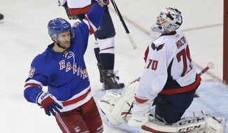 New York Rangers' Dominic Moore (28) celebrates a goal by Jarret Stoll (26) as Washington Capitals goalie Braden Holtby (70) reacts during the third period of an NHL hockey game Tuesday, Nov. 3, 2015, in New York. The Rangers won 5-2. (AP Photo/Frank Franklin II)