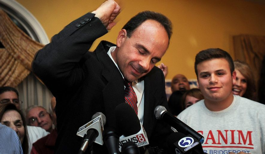Democrat Joe Ganim celebrates with his son Rob and other supporters after winning the election as Bridgeport's new mayor at Testo's Restaurant in Bridgeport, Conn., Tuesday, Nov. 3, 2015. Ganim, an ex-convict who spent seven years in federal prison for corruption, reclaimed the Bridgeport mayor's office Tuesday, completing a stunning comeback bid that tapped nostalgia for brighter days in Connecticut's largest city. (Brian A. Pounds/Hearst Connecticut Media via AP) MANDATORY CREDIT