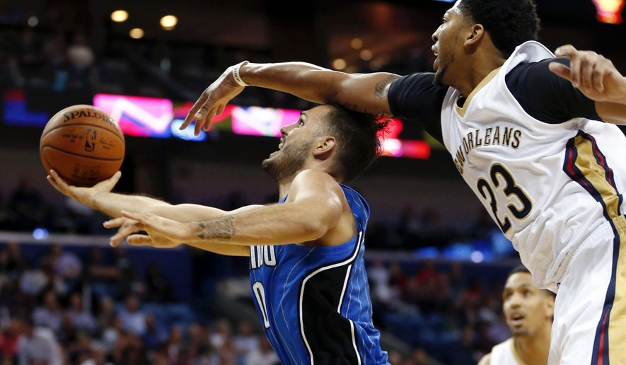 Orlando Magic forward Evan Fournier, left, goes to the basket against New Orleans Pelicans forward Anthony Davis (23) in the first half of an NBA basketball game in New Orleans, Tuesday, Nov. 3, 2015. (AP Photo/Gerald Herbert)
