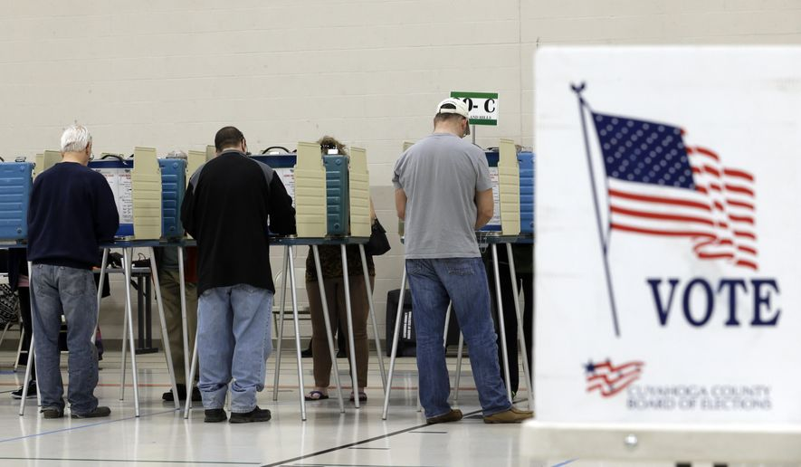 Voters cast their vote at the athletic wing of Orange High School Tuesday, Nov. 3, 2015, in Moreland Hills, Ohio. Election officials in two of Ohio's counties say lines of voters dwindled some after an early wave of Ohioans who cast their ballots early in the state's general election. (AP Photo/Tony Dejak)