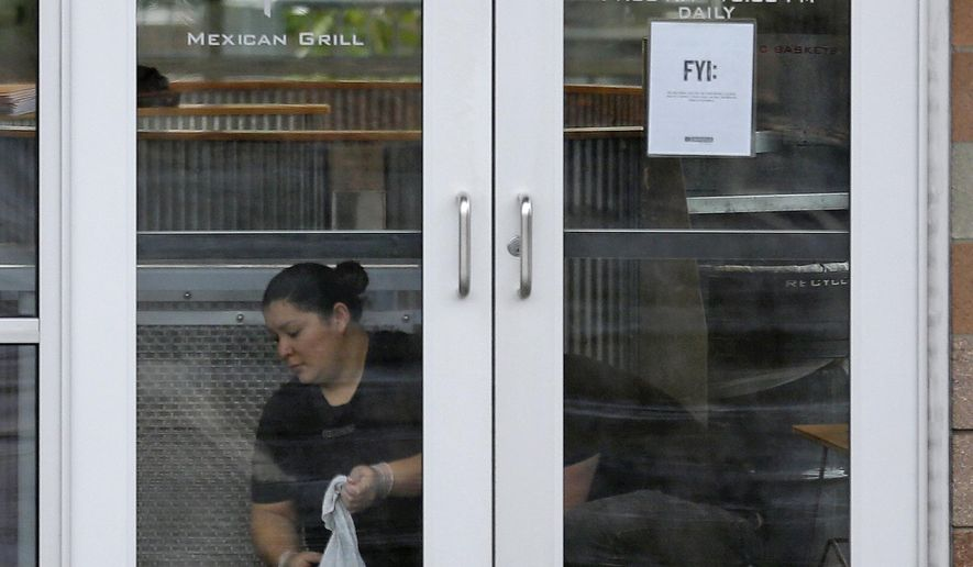 A worker cleans inside a closed Chipotle restaurant, Tuesday, Nov. 3, 2015, in Federal Way, Wash. Chipotle closed 43 of its Pacific Northwest locations after the chain's third foodborne illness this year sickened about two dozen people. (AP Photo/Ted S. Warren)