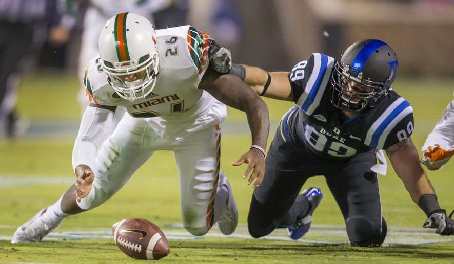 Miami's Rayshawn Jenkins, left, recovers a fumble by Duke's Max McCaffrey as Duke's Braxton Deaver, right, scrambles for the ball during the first half of an NCAA college football game, in Durham, N.C., Saturday, Oct. 31, 2015. (AP Photo/Rob Brown)