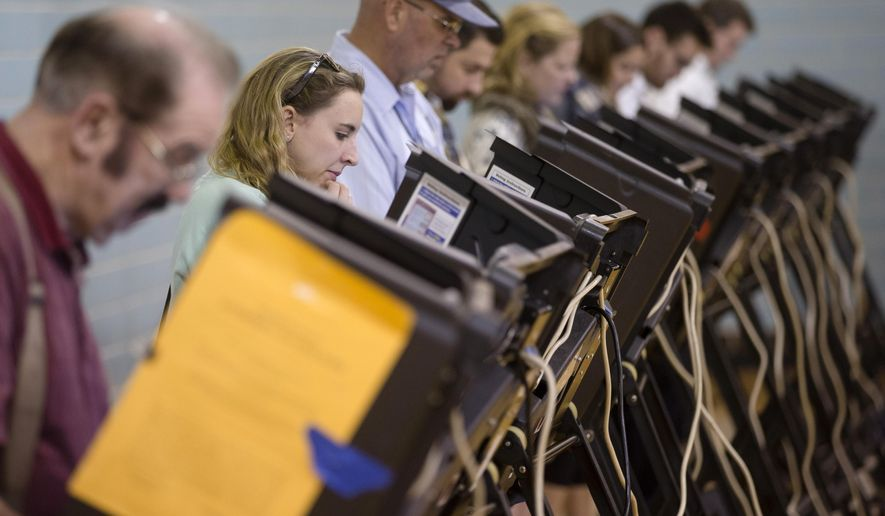 Voters use electronic voting machines at the Schiller Recreation Center polling station on election day, Tuesday, Nov. 3, 2015, in Columbus, Ohio. Eligible Ohioans headed to the polls Tuesday, to decide whether to make marijuana legal for both recreational and medical use. (AP Photo/John Minchillo)