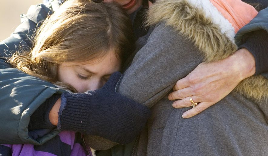 In this photo taken on Saturday, Nov. 6, 2010, Vanderburgh County Coroner Annie Groves, center,  gives Autumn Marx, 11, left and her sister, Leah Marx, 14, right a hug at the Eastbrook Tornado Memorial Park and Playground, in Evansville, Ind. The Marx girls lost their mother, Brandy Morefield, as a result of the November 6 tornado five years ago. The girls were not at home with their mother the night of the tornado. Morefield was critically injured in the tornado and died at St. Mary's Medical Center days later. (Erin McCracken/Evansville Courier & Press via AP) MANDATORY CREDIT