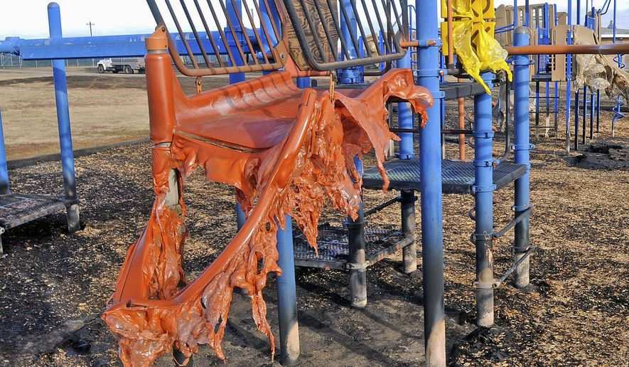 FILE - This Oct. 12, 2015 file photo shows melted playground equipment after a prairie fire outside Cannon Ball Elementary School in Cannon Ball, N.D.  Students at the school who were displaced when the grass fire affected their elementary school on the Standing Rock Indian Reservation last month have returned to their regular classrooms. The blaze melted playground equipment and filled the school with smoke and soot. The 115 students attended classes in nearby Solen during the three weeks of cleanup. (Tom Stromme/Bismarck Tribune via AP, File) MANDATORY CREDIT
