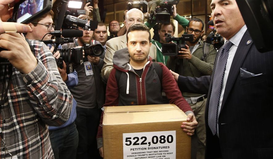 """Juan Escalante, campaign manager for the immigration reform group America's Voice, carries a box he claims contains over half a million petition signatures demanding that NBC revoke the invitation for Republican presidential candidate Donald Trump to be a guest-host on this weekend's """"Saturday Night Live,"""" into NBC Studios where the show is taped and broadcast, Wednesday, Nov. 4, 2015 in New York.  Pressure from a coalition of advocacy groups continued to mount on NBC to cancel Trump's appearance.  (AP Photo/Kathy Willens)"""