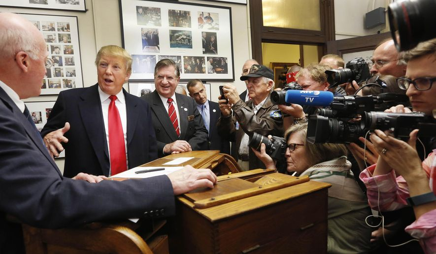 Republican presidential candidate Donald Trump talks with New Hampshire Secretary of State Bill Gardner before filing papers to be on the nation's earliest presidential primary ballot, Wednesday, Nov. 4, 2015, at The Secretary of State's office in Concord, N.H. (AP Photo/Jim Cole)