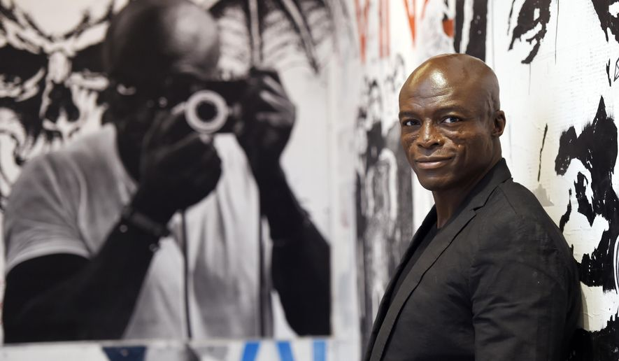 "In this Monday, Oct. 5, 2015 photo, singer/songwriter Seal poses in front of a mural of musicians including himself at left at Warner Bros. Records in Burbank, Calif.  ""Seal 7"" is the artist's first new music in five years: an album about love, heartbreak and healing. (Photo by Chris Pizzello/Invision/AP)"