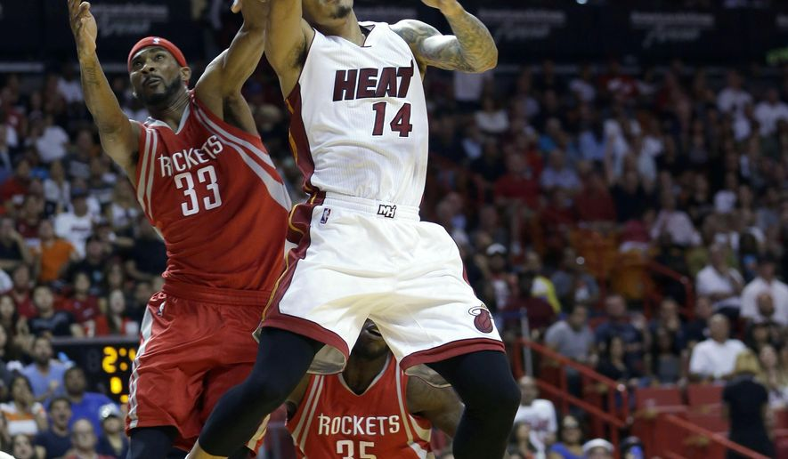 Miami Heat guard Gerald Green (14) is fouled by Houston Rockets guard Corey Brewer (33) as he goes to the basket in the second half of an NBA basketball game, Sunday, Nov. 1, 2015, in Miami. The Heat won 109-89. (AP Photo/Alan Diaz)
