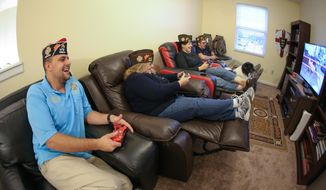 From left, Britton Shoellhorn, Christine Mauler, Hollie Shoellhorn, and Ryan Golden play video games in an upstairs loft at a new VFW that has formed in the Shoellhorn residence in Greenwood, In.  To fill a need in the community, Hollie Shoellhorn has helped form a new VFW in Johnson County, focused on appealing to a younger generation as well as older veterans in the area.  (Chris Williams/Daily Journal via AP)