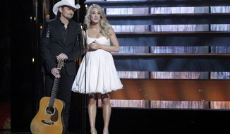 In this Nov. 5, 2014 photo, hosts Brad Paisley, left, and Carrie Underwood appear at the 48th annual CMA Awards in Nashville, Tenn. The pair return to host another CMA Awards event, Wednesday, Nov. 4, 2015, which includes three days of rehearsals.  (Photo by Wade Payne/Invision/AP, File)