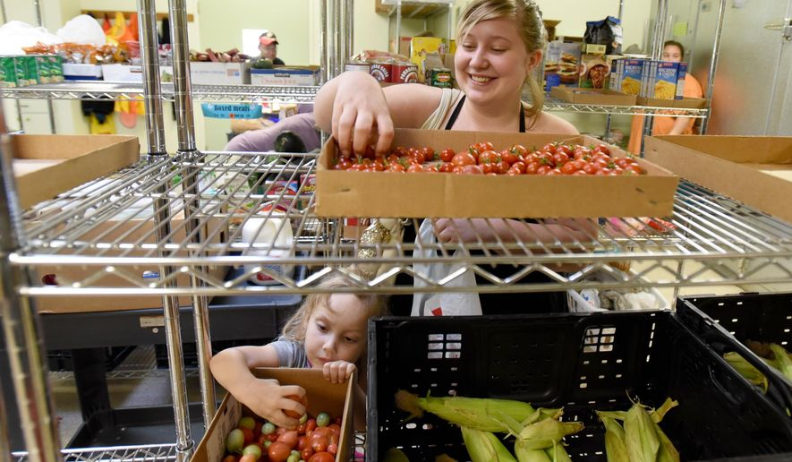 In this Sept. 29, 2015, photo, Courtney Wood and her daughter Kaydence Chaffin, pick up some produce at the Nazarene Care House in Nampa, Idaho. Neal Moore, director of the care house, said many people from all walks of life come looking for help every day. (Adam Eschbach/The Idaho Press-Tribune via AP)  MANDATORY CREDIT