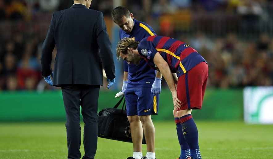 Barcelona's Ivan Rakitic grimaces and holds his thigh after injuring himself during the Champions League Group E soccer match between FC Barcelona and BATE Borisov at the Camp Nou stadium in Barcelona, Spain, Wednesday, Nov. 4, 2015. (AP Photo/Manu Fernandez)