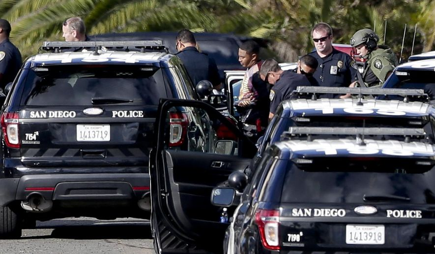A suspect in a shooting, center, identified by police as Titus Colbert, is escorted away from an apartment building after an hours-long standoff with officials Wednesday, Nov. 4, 2015, in San Diego. Flights to the San Diego International Airport resumed after police took the gunman, who fired shots at a nearby apartment complex, posing a threat to air traffic, into custody. (AP Photo/Gregory Bull)