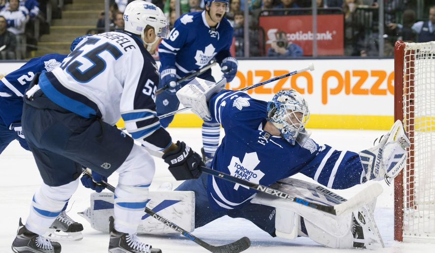 Toronto Maple Leafs' goaltender James Reimer, right, stretches to make the save on a goal by Winnipeg Jets' Mark Scheifele, left, during the first period of an NHL hockey game in Toronto, Wednesday, Nov. 4, 2015. (Darren Calabrese/The Canadian Press via AP) MANDATORY CREDIT