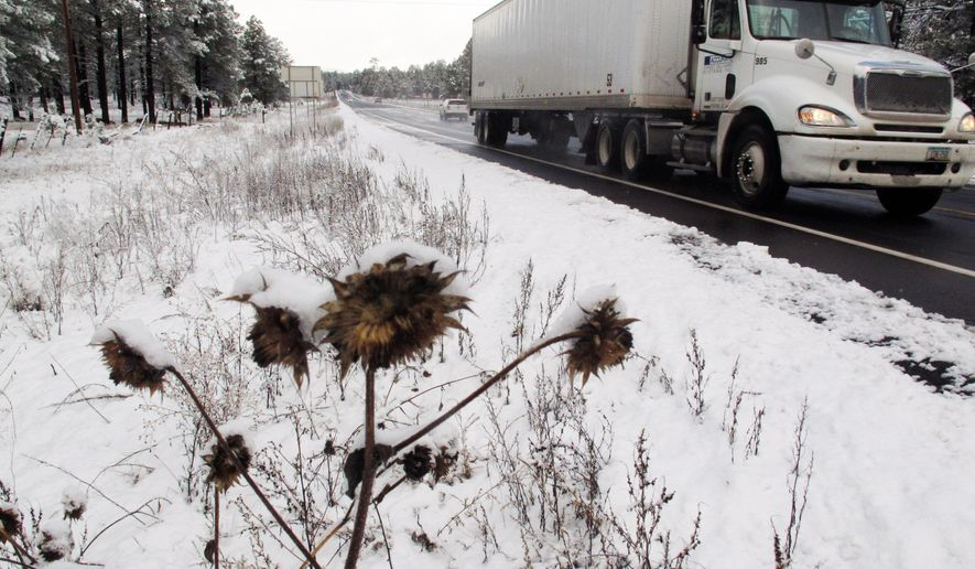 A truck drives down a slippery orad as snowy weather made travel slow in Flagstaff, Ariz., on Wednesday, Nov. 4, 2015, during the city's first snowfall of the season. Northern Arizona is getting an early taste of winter weather, with snow falling in Flagstaff and making roads and highways slippery.  .(AP Photo/Felicia Fonseca)