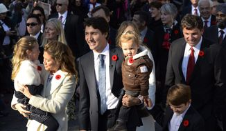 Prime Minister-designate Justin Trudeau, his wife Sophie Gregoire-Trudeau and their children Ella-Grace, Hadrien and Xavier lead the new Liberal cabinet to Rideau Hall in Ottawa on Wednesday, Nov. 4, 2015. Trudeau has been sworn in as Canada's next prime minister, following in the footsteps of his storied father. (Sean Kilpatrick/The Canadian Press via AP)