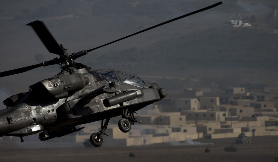 A US AH-64 Apache flies over the combat zone during a NATO military demonstration in Zaragoza, Spain, Wednesday Nov. 4, 2015. (AP Photo/Abraham Caro Marin)