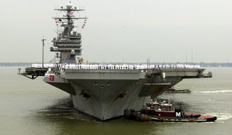 FILE - In this May 29, 2003 file photo, sailors man the rails as the USS Theodore Roosevelt is maneuvered into it's berth at the Norfolk Naval Station in Norfolk, Va. Defense Secretary Carter was flying Thursday onto the USS Theodore Roosevelt, an American aircraft carrier in the disputed waterway. Carter is using the visit to the USS Theodore Roosevelt to amplify the U.S. view that China is making excessive claims that nearly all of the South China Sea as its territory.  (AP Photo/Steve Helber, File)