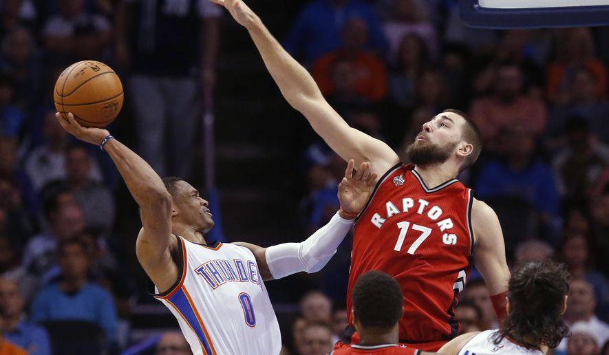 Oklahoma City Thunder guard Russell Westbrook (0) shoots as Toronto Raptors center Jonas Valanciunas (17) defends during the second quarter of an NBA basketball game in Oklahoma City, Wednesday, Nov. 4, 2015. (AP Photo/Sue Ogrocki)