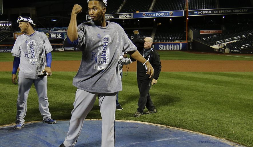 Kansas City Royals' Alcides Escobar, right, poses on the New York Mets logo after Game 5 of the Major League Baseball World Series against the New York Mets Monday, Nov. 2, 2015, in New York. The Royals won 7-2 to win the series. (AP Photo/Matt Slocum)