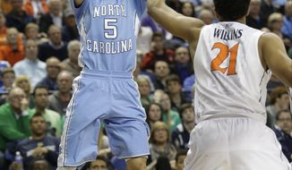 FILE - In this March 13, 2015, file photo, North Carolina's Marcus Paige (5) shoots over Virginia's Isaiah Wilkins (21) during the second half of an NCAA college basketball game in the semifinals of the Atlantic Coast Conference tournament in Greensboro, N.C. Top-ranked North Carolina has lost senior guard Marcus Paige to a broken right hand for three to four weeks. The school announced Paige's injury Wednesday, Nov. 4, 2015, saying the preseason Atlantic Coast Conference co-player of the year broke a bone in his non-shooting hand during Tuesday's practice. (AP Photo/Bob Leverone, File)
