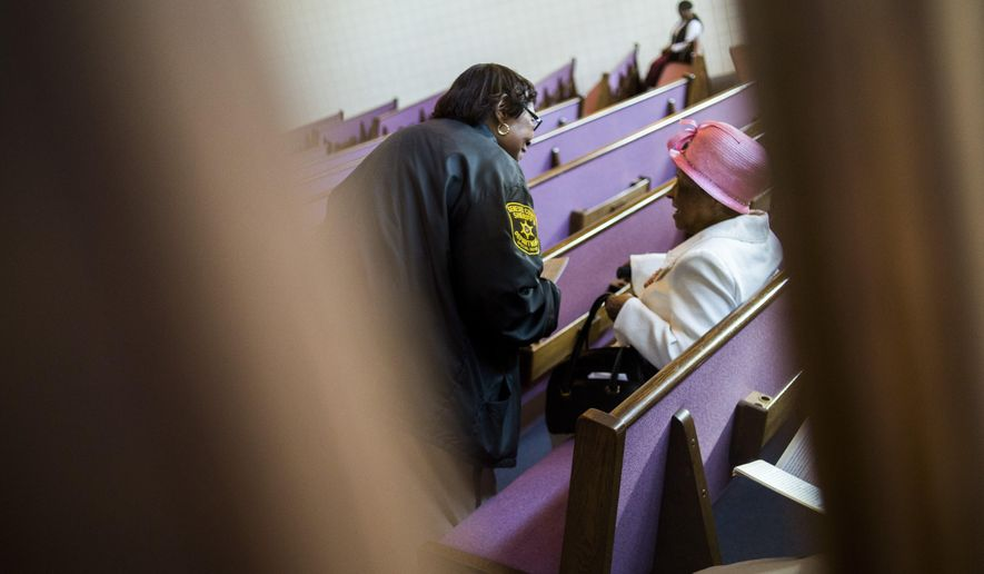 In a Sunday, Oct. 11, 2015 photo, deputized volunteers assist church-goers at Mt. Calvary Church on Flint's north side as part of the Security in Ministry program, which will celebrate its 27th anniversary this month. The program began in the 1980s when a Flint pastor asked the sheriff to train some church-going volunteers to protect members and their property during services. (Jake May/The Flint Journal-MLive.com via AP) LOCAL TELEVISION OUT; LOCAL INTERNET OUT; MANDATORY CREDIT