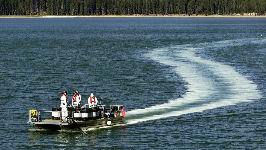 FILE - In this Sept. 14, 2006 file photo, Oregon Department of Fish and Wildlife employees leave a trail of the pesticide Rotenone, used to kill tui chub fish, in the waters of Diamond Lake, Ore.  Biologists have found a tui chub at Diamond Lake nine years after the expensive project to eliminate the invasive minnow. Biologists believe tui chub were used illegally as live bait or were intentionally reintroduced into the lake.  (Jim Craven/The Mail Tribune via AP, file)  MANDATORY CREDIT