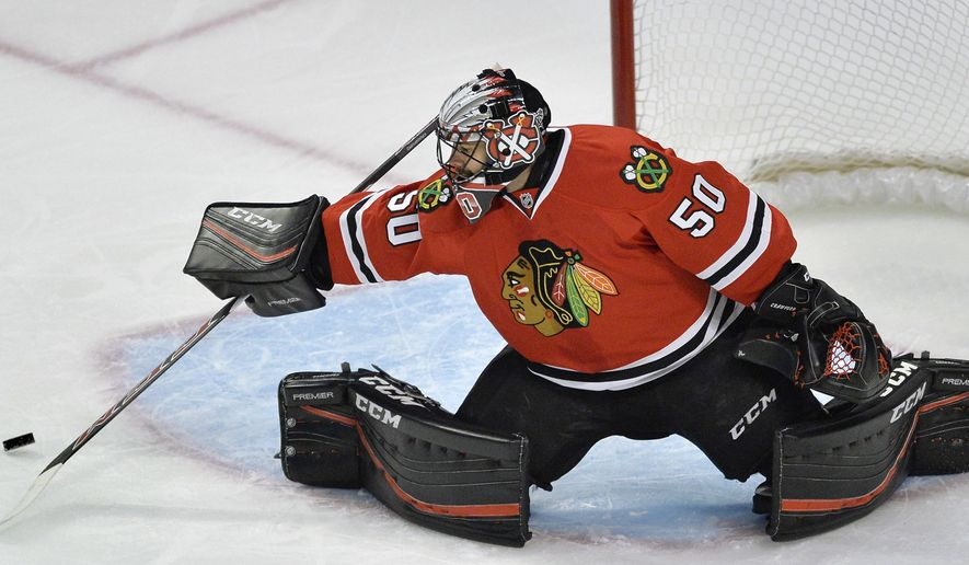 RETRANSMISSION TO CORRECT DATE - Chicago Blackhawks goalie Corey Crawford (50), makes a save during the first period of a hockey game against the St. Louis Blues Wednesday, Nov. 4, 2015, in Chicago. (AP Photo/Paul Beaty)
