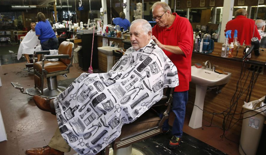 In this Sept. 11, 2015 photo, longtime resident John Soderstrom gets a trim at Barney's barber shop in Ponca City, Okla. The latest oil boom, fueled by horizontal hydraulic fracturing that enabled drillers to tap deep, previously inaccessible oil deposits, brought many back to the oil fields for a big payday. Soderstrom says Welders could make $50 to $75 an hour. (AP Photo/Sue Ogrocki)