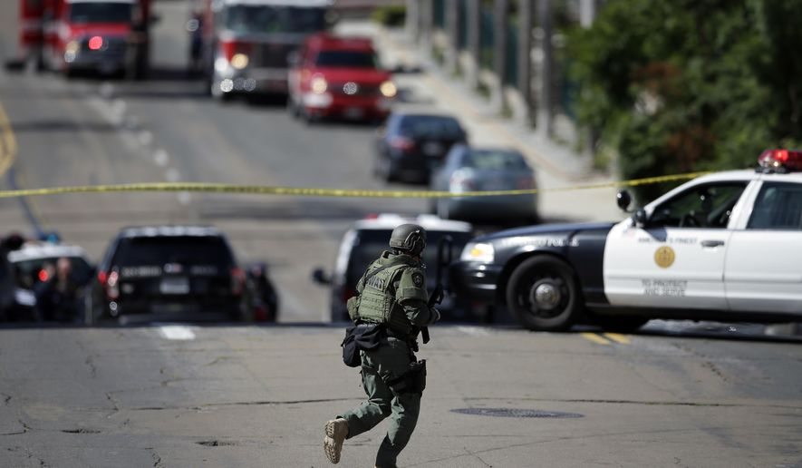 A San Diego police officer patrols a neighborhood in San Diego on Wednesday, Nov. 4, 1015. A man with a high-powered gun was firing sporadically inside a San Diego apartment complex, causing the city's nearby airport to stop planes from landing, authorities said. Officers swarmed the building and exchanged gunfire with the man. (AP Photo/Greg Bull)