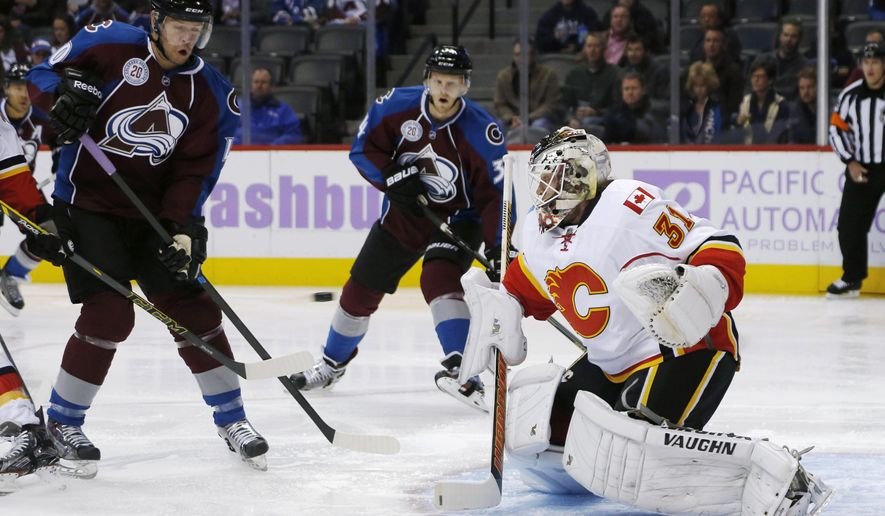 Calgary Flames goalie Karri Ramo, right, of Finland, stops a shot as Colorado Avalanche left wing Alex Tanguay, left, and center Carl Soderberg, back, of Sweden, watch during the first period of an NHL hockey game Tuesday, Nov. 3, 2015, in Denver. (AP Photo/David Zalubowski)