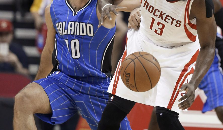 Orlando Magic's Evan Fournier (10) tries to get the ball from Houston Rockets' James Harden (13) during the first half of an NBA basketball game Wednesday, Nov. 4, 2015, in Houston. (AP Photo/Pat Sullivan)