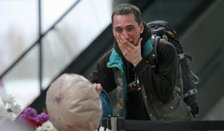 A man reacts as he stands next to flowers and toys at an entrance of Pulkovo airport outside St. Petersburg, Russia during a day of national mourning for the victims of Saturday's plane crash over Egypt Wednesday, Nov. 4, 2015. (AP Photo/Dmitry Lovetsky)