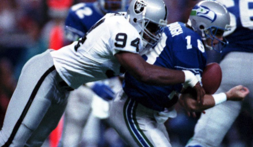 FILE - In this Oct. 18, 1992, file photo, Los Angeles Raiders' Anthony Smith (94) sacks Seattle Seahawks quarterback Stan Gelbaugh during the second quarter of an NFL football game in Seattle. Smith, a former defensive end with the Oakland and Los Angeles Raiders, has been found guilty Thursday, Nov. 5, 2015,  in the shooting deaths of two brothers in 1999 and the stabbing death of another man in 2001. Prosecutors say all three had been kidnapped and tortured. His attorney, Michael Evans, says he'll appeal the convictions.  (AP Photo/Gary Stewart)