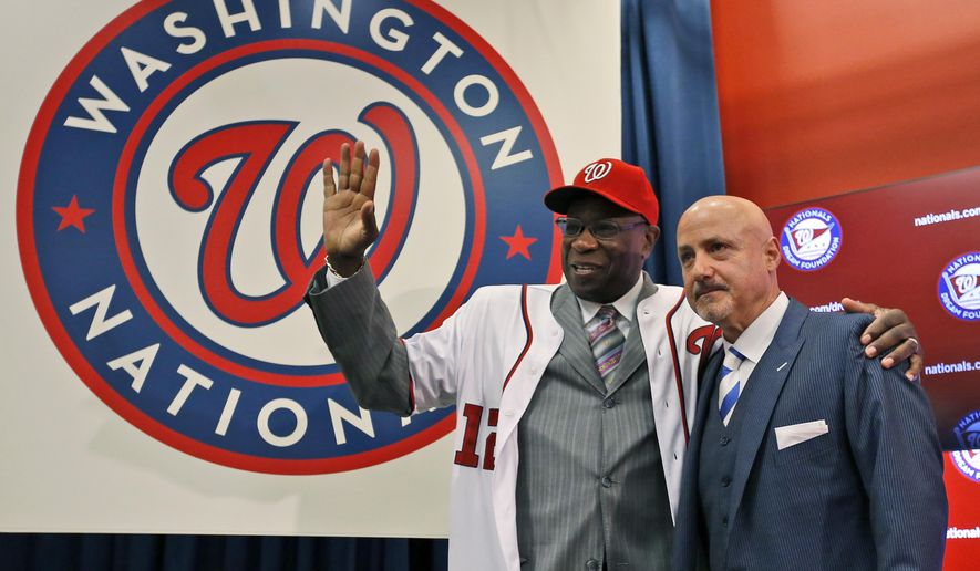 Dusty Baker, left, with general manager Mike Rizzo,  waves after he was presented with his hat and jersey, during a news conference to present Baker as the new manager of the Washington Nationals baseball team, Thursday, Nov. 5, 2015, in Washington. (AP Photo/Alex Brandon)
