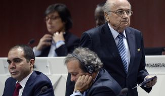 FILE - In this May 29, 2015 file photo FIFA president Joseph S. Blatter, right, walks past Prince Ali bin al-Hussein, left, and UEFA President Michel Platini, center, during the 65th FIFA Congress held at the Hallenstadion in Zurich, Switzerland. In a FIFA election that is now more open than expected, Prince Ali bin al-Hussein has had to change strategy since Michel Platini was caught up in a corruption allegation, it was reported on Thursday, Nov. 5, 2015. Prince Ali struck a more cautious note in an interview with the Associated Press than the fighting talk he directed at Platini before the one-time election favorite was quizzed in a Swiss criminal investigation of a $2 million payment from FIFA in 2011. (Walter Bieri/Keystone via AP, File)