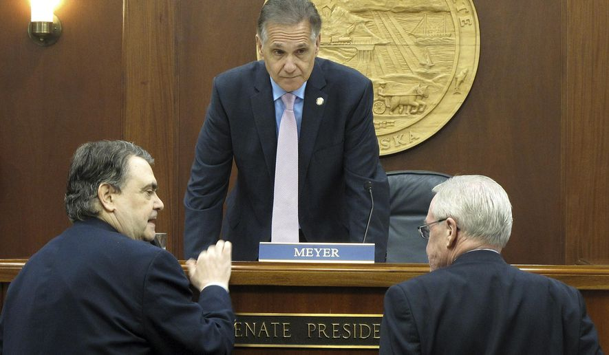 Alaska Senate President Kevin Meyer, center, speaks with Sens. Johnny Ellis, left, and Dennis Egan after the Senate adjourned from a special session called to consider the buyout of one of the state's partners in a proposed gas project, bringing the session to an official close on Thursday, Nov. 5, 2015, in Juneau, Alaska. The House adjourned on Wednesday. During the session, the Legislature approved a measure authorizing funding for the buyout of TransCanada Corp.'s interest in the project. (AP Photo/Becky Bohrer)