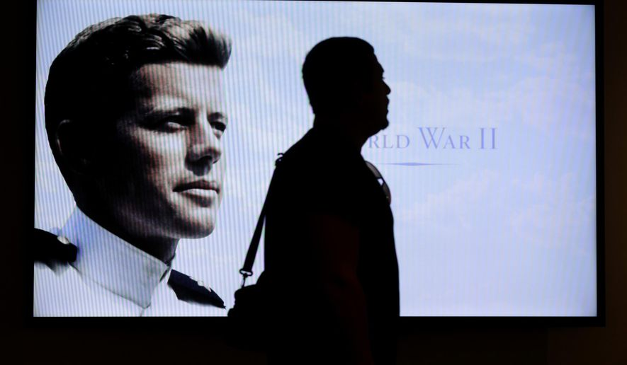 """Museum visitor Edmilson Da Cruz, of Hayward, Calif., center, is silhouetted in front of a World War II era photograph of John F. Kennedy in an exhibit  titled """"Young Jack"""" at the John F. Kennedy Presidential Library and Museum, Thursday, Nov. 5, 2015, in Boston. The new exhibit is devoted to the 35th U.S. president's early years. (AP Photo/Steven Senne)"""