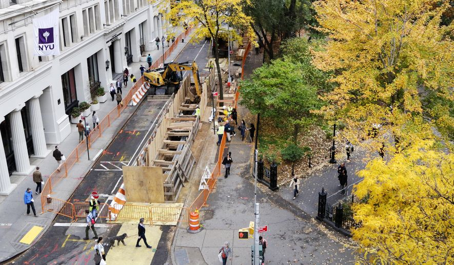 A plywood wall surrounds the opening to an underground construction area, Thursday, Nov. 5, 2015 in the Greenwich Village neighborhood of New York. Two burial vaults discovered beneath a street in the heart of New York University's campus by workers replacing a water main were likely part of a Presbyterian church cemetery, an archaeologist said Thursday. (AP Photo/Mark Lennihan)