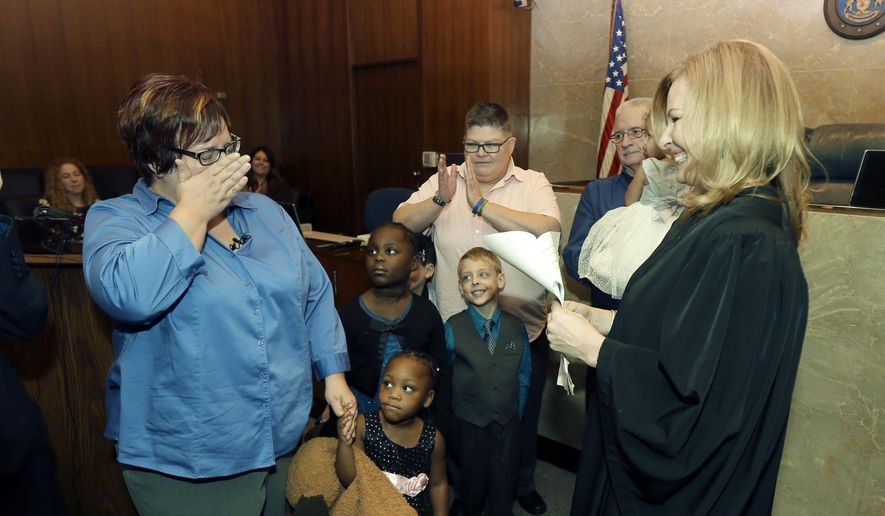 In this file photo from 2015, April DeBoer, left, wipes away tears before Judge Karen McDonald, right, and DeBoer's spouse Jayne Rowse, center, after an adoption ceremony at the Oakland County Circuit Court, Thursday, Nov. 5, 2015, in Pontiac, Mich. A bill in the Tennessee state legislature would allow faith-based orphanages and child-placement organizations to decline adoptions or foster care based on religious beliefs, including opposition to LGBT parents. (AP Photo/Carlos Osorio) **FILE**