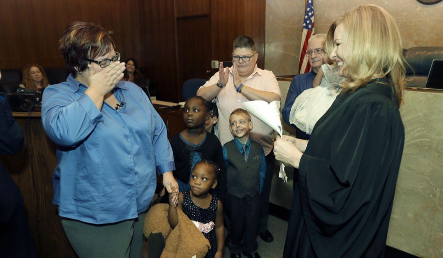 April DeBoer, left, wipes away tears before Judge Karen McDonald, right, and DeBoer's spouse Jayne Rowse, center, after an adoption ceremony at the Oakland County Circuit Court, Thursday, Nov. 5, 2015, in Pontiac, Mich. DeBoer and Rowse, the same-sex couple from Michigan has jointly adopted five children, closing a case that started when they challenged the state's restrictions on adoption and helped pave the way for the landmark U.S. Supreme Court decision allowing gay marriage. The couple are raising the children at their Hazel Park home. They sued the state in 2012, initially challenging Michigan's restrictions on joint adoption and later the ban on gay marriage at the suggestion of the judge in the case. (AP Photo/Carlos Osorio)