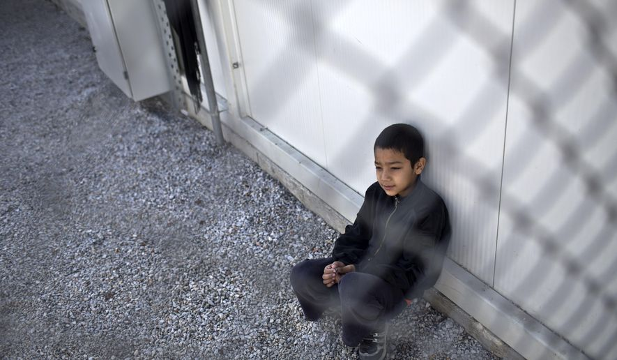 A boy sits inside an enclosure at the migrant and refugee registration camp in Moria, on the island of Lesbos, Greece, Thursday, Nov. 5, 2015.  The European Union predict that around 3 million more migrants are expected to arrive in the 28-nation bloc by the end of next year. (AP Photo/Marko Drobnjakovic)