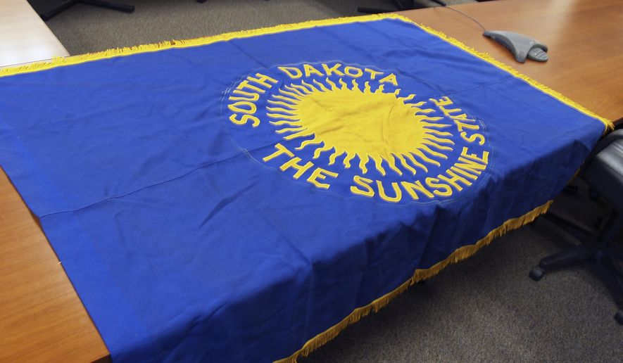This Oct. 13, 2015 file photo provided by the South Dakota Attorney General's office in Sioux Falls, S.D., shows the front side of the original South Dakota state flag that was recovered after it had been missing since January 2015. Garrett DeVries, 26, a former Secretary of State employee accused of stealing the flag has been put on leave by the Washington, D.C.-area Republican research company where he works. Devries has been charged with one count of theft having a value in excess of $400. He is on leave pending the outcome of his appearance in state court in Pierre, S.D., on Nov. 23, 2105. (South Dakota Attorney General's office via AP, File)
