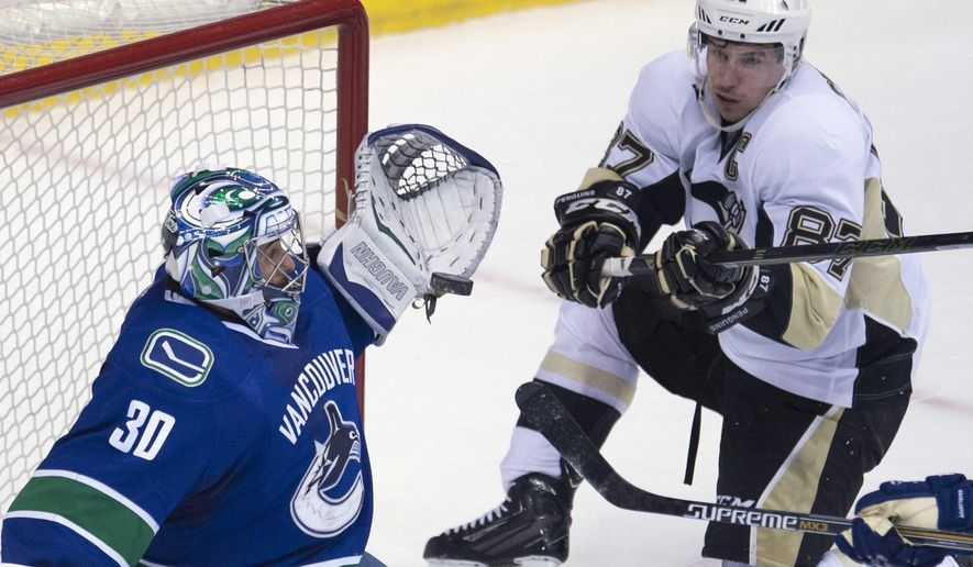 Pittsburgh Penguins' center Sidney Crosby, right, tries to get a shot past Vancouver Canucks goalie Ryan Miller (30) during the second period of an NHL hockey game Wednesday, Nov. 4, 2015, in Vancouver, British Columbia. (Jonathan Hayward/The Canadian Press via AP)