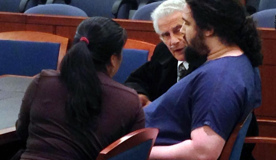 Defendant Joey Kadmiri, center, confers Thursday, Nov. 5, 2015, with defense attorneys Yi Lin Zheng, left, and John Momot, in Clark County District Court in Las Vegas. Kadmiri, 26, pleaded guilty to three felony charges in a March, 2014 backstage shooting and theft of costumes and props from the Thunder From Down Under male revue on the Las Vegas Strip.(AP Photo/Ken Ritter)