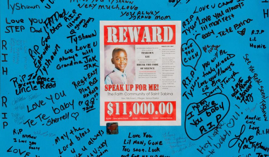 A reward sign and messages hang Wednesday, Nov. 4, 2015, near where Tyshawn Lee was fatally shot in Chicago. Lee, 9, was shot Monday in the Auburn Gresham neighborhood. (AP Photo/Teresa Crawford)